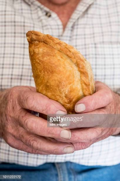a man holding a fresh homemade pasty with a crimped edge, a regional speciality - cornish pasty stock pictures, royalty-free photos & images