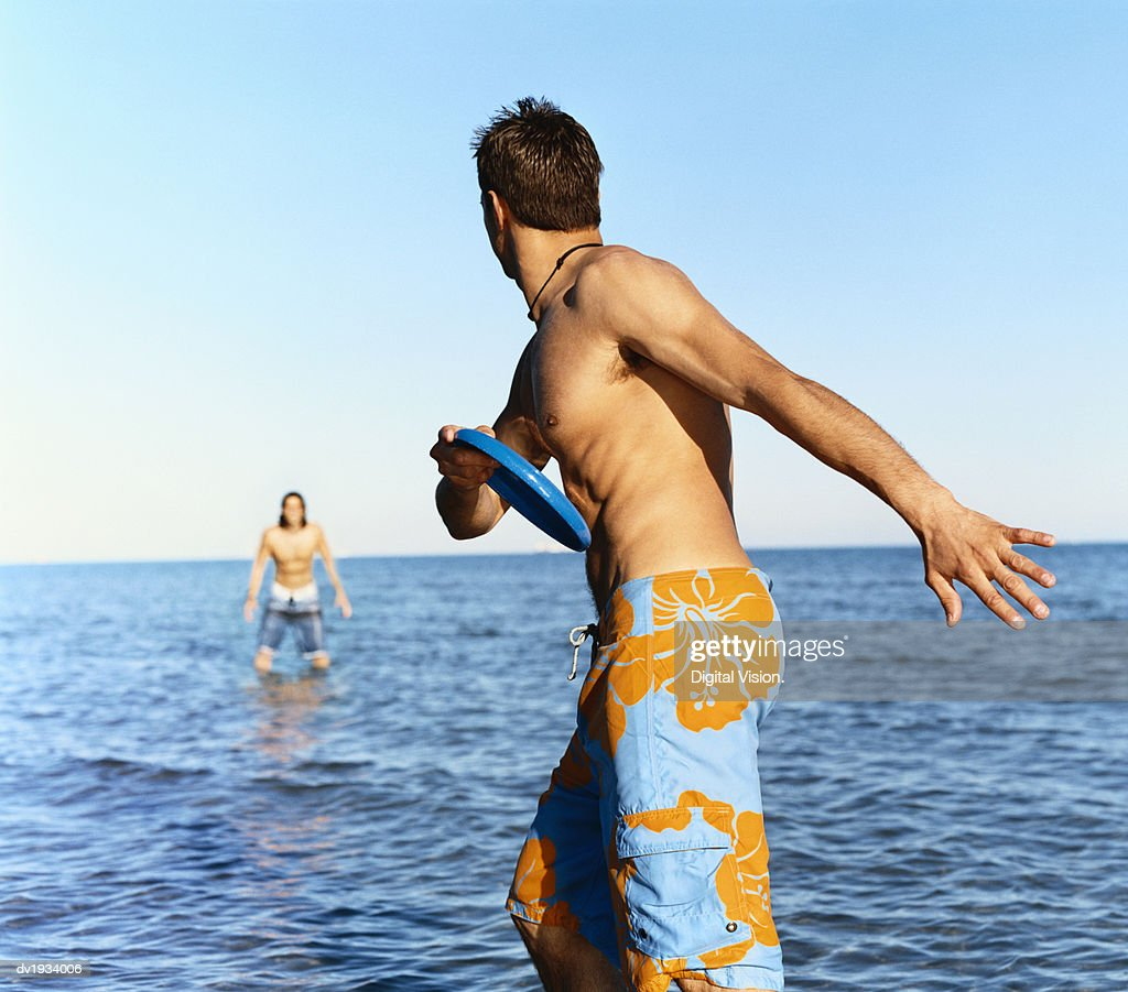 Man Holding a Frisbee in the Sea, Other Man in the Background : Stock Photo