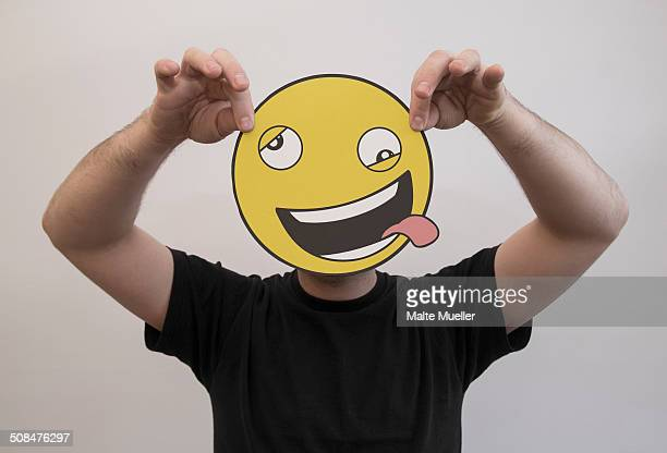 Man holding a funny emoticon face in front of his face