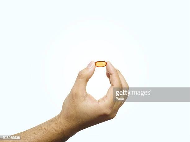 man holding a gel capsule. - tenir photos et images de collection
