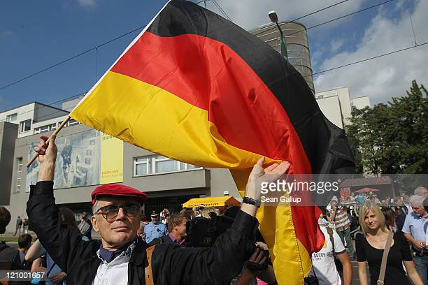 A man holding a German flag attends a ceremony commemorating the 50th anniversary of the construction of the Berlin Wall at the Bernauer Strasse...