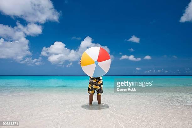 man holding a giant beach ball on tropical beach - ビーチボール ストックフォトと画像
