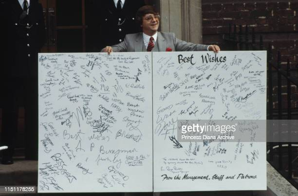 A man holding a giant card at the Lindo Wing of St Mary's Hospital in London June 1982 The card is signed by the management staff and patrons of the...