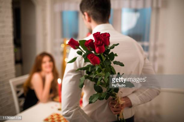 man holding a gift for his girlfriend - valentines day stock pictures, royalty-free photos & images