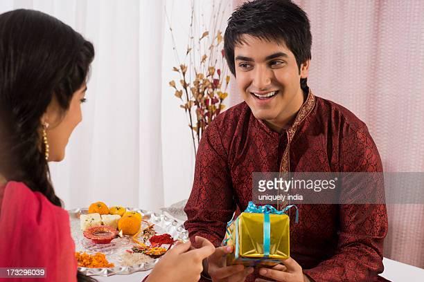 Man holding a gift while his sister holding a puja thali at Raksha Bandhan