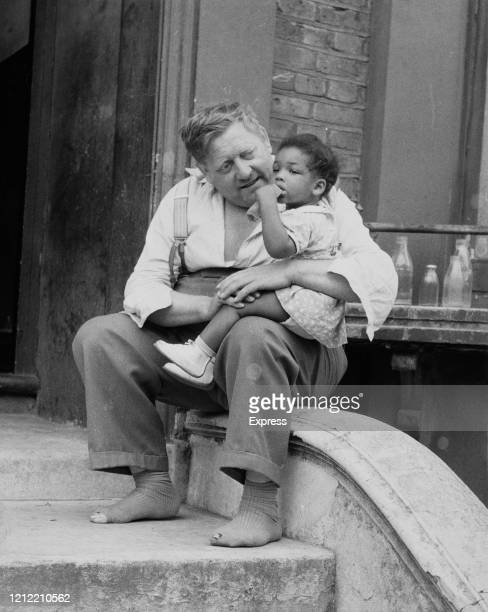 Man holding a girl in Notting Hill during the race riots, London, UK, 3rd September 1958.