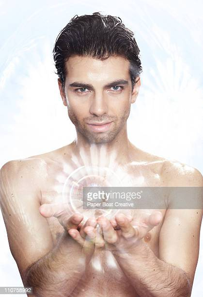 Man holding a glowing ball cupped in his hands