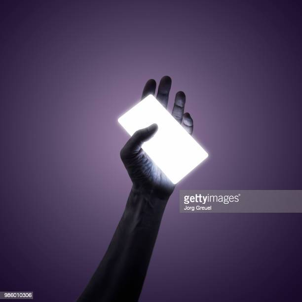 man holding a glowing smart phone - glowing stock pictures, royalty-free photos & images