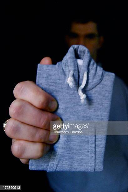 CONTENT] A man holding a grey hoodie notebook in front of himself with his hand