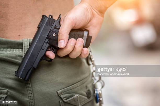 a man holding a gun on his back. the gunman held his gun behind him.crime concept.criminality concept. - kidnapping stock pictures, royalty-free photos & images