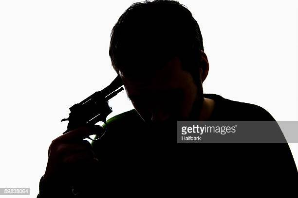a man holding a gun to his head - suicide stock photos and pictures