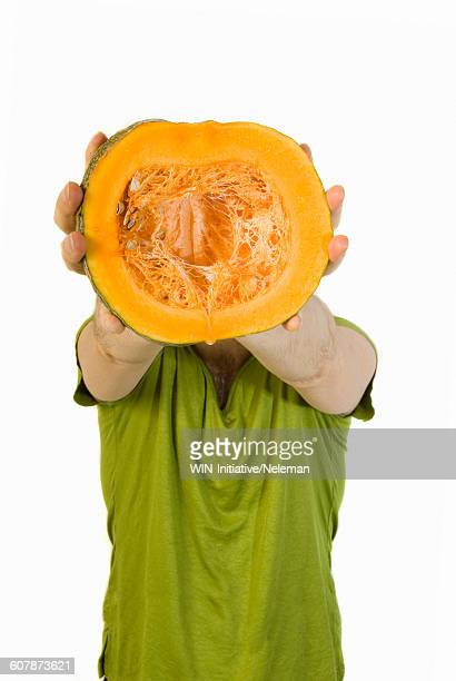 Man holding a half of a pumpkin in front of his face