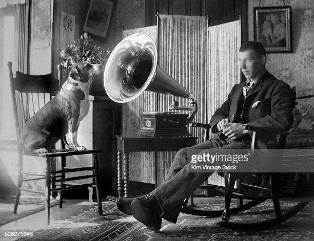 A man holding a harmonica and beagle sitting on a chair listen to the sounds coming from a cylinder phonograph The photograph recalls the trademarked...