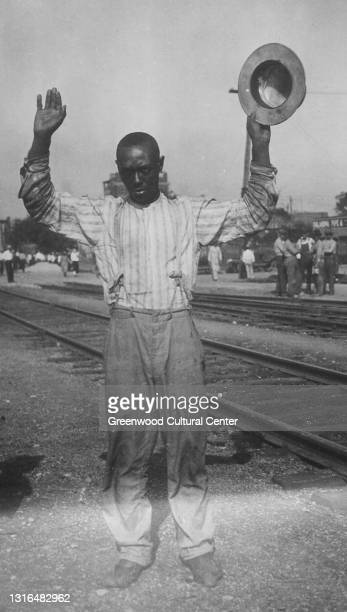 Man holding a hat with his hands up wearing suspenders surrenders during the Tulsa Race Massacre which occurred from May 31, 1921 through June 1,...