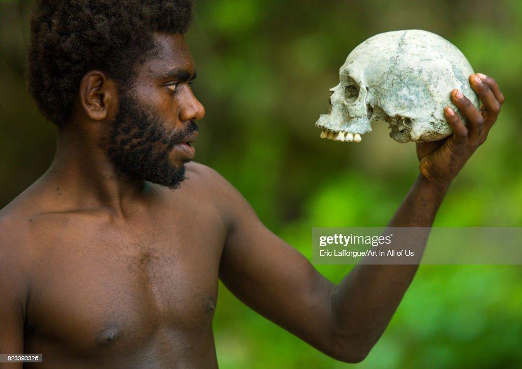 Man holding a human skull in Amelbati cannibal site, Malampa Province, Malekula Island, Vanuatu on August 27, 2007 in Malekula Island, Vanuatu.
