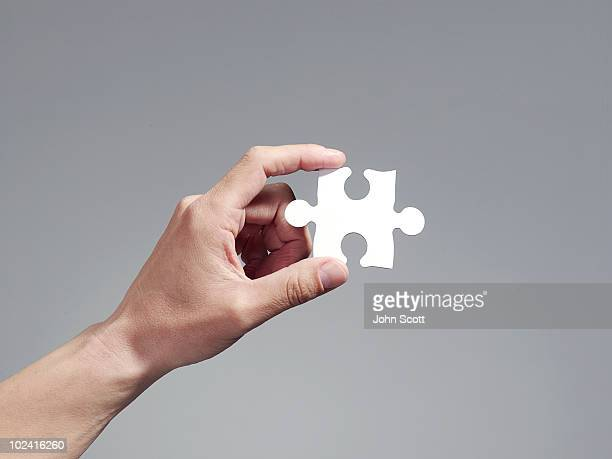 Man holding a jigsaw puzzle piece