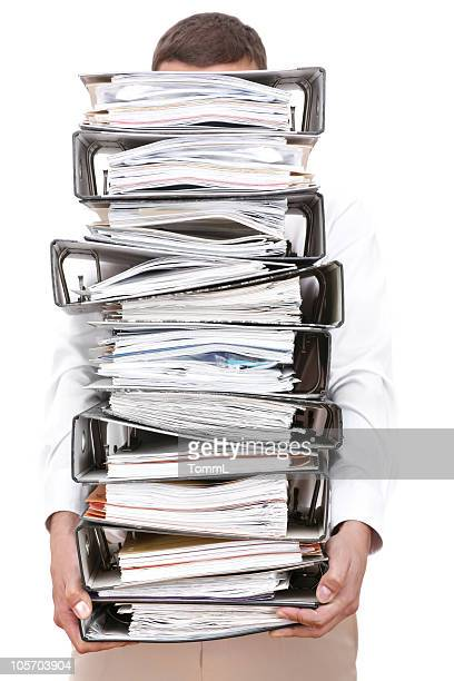 A man holding a large pile of binders filled with papers.
