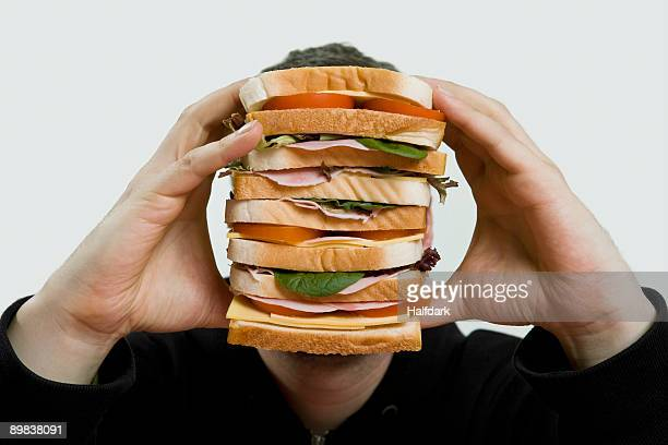 a man holding a large sandwich - over eating stock pictures, royalty-free photos & images