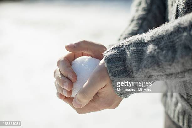 A man holding a large snowball in his bare hands.