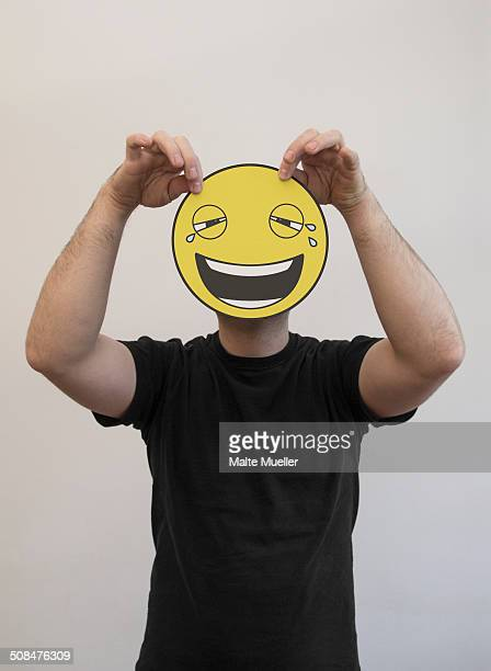 man holding a laughing and crying emoticon face in front of his face - smiley face stock pictures, royalty-free photos & images