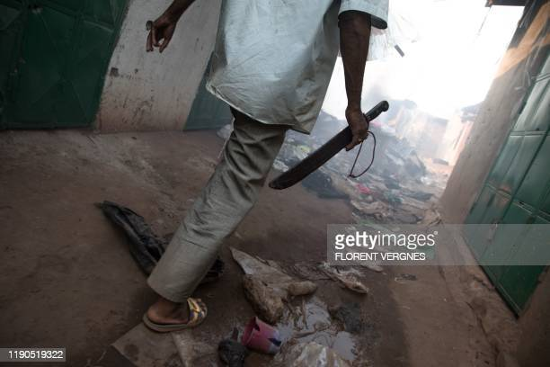Man holding a machete walks between ransacked houses in the PK5 district in Bangui on December 26 after clashes erupted when traders took up arms to...