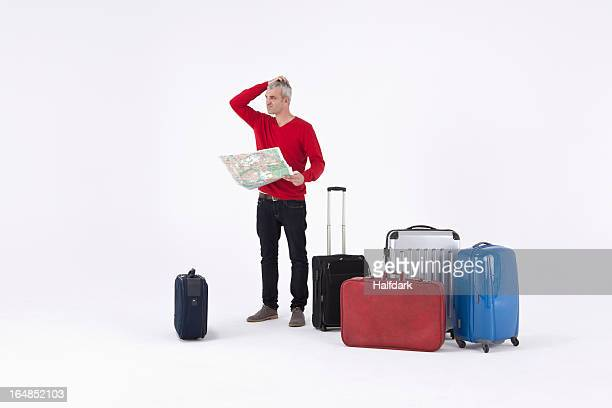 A man holding a map and scratching his head, surrounded by luggage