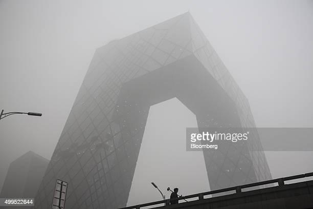 A man holding a monitoring device walks past the China Central Television headquarters building shrouded in haze in Beijing China on Tuesday Dec 1...