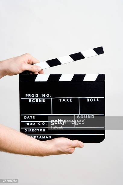 a man holding a movie clapperboard - clapboard stock pictures, royalty-free photos & images