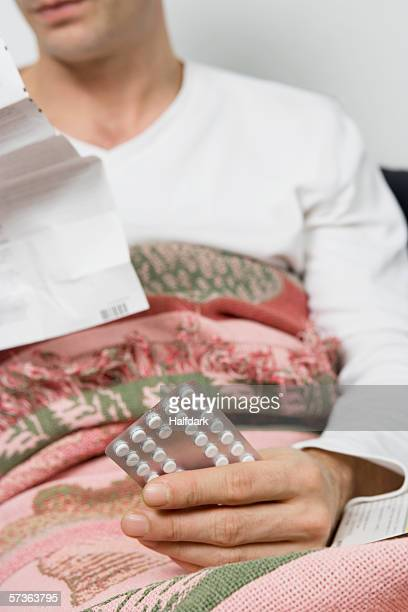 A man holding a package of pills in bed