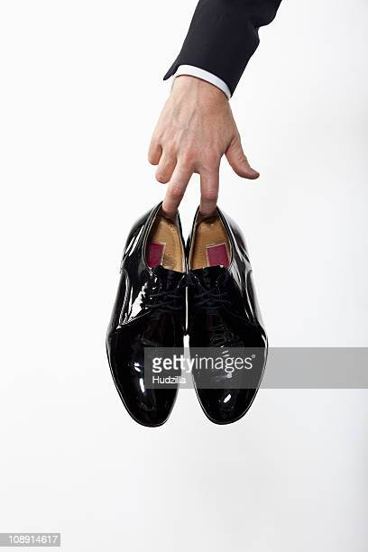 a man holding a pair of patent leather dress shoes, focus on hand - nette schoen stockfoto's en -beelden