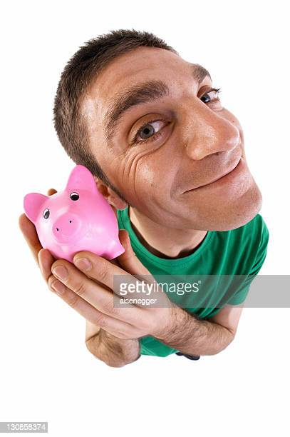 Man holding a piggy bank to his ear, fish-eye lens