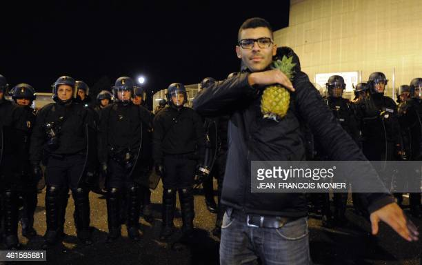 A man holding a pineapple performs a quenelle salute in front of a line of French police officers after the performance of French controversial...