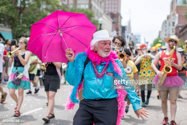 A man holding a pink umbrella dances down Boylston St during the 2018 Boston Pride Parade on June 9 2018 in Boston Massachusetts