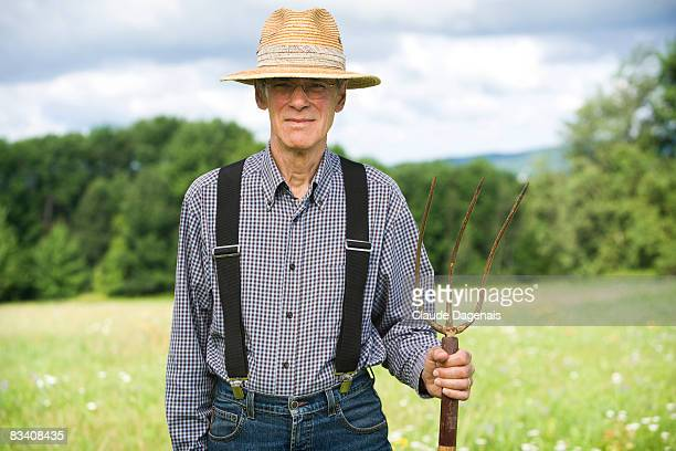 Man holding a pitchfork in the middle of a field.
