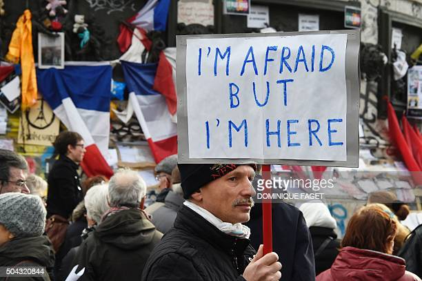 A man holding a placard reading 'I am afraid but I am here' during a gathering on Place de la Republique on January 10 2016 in Paris as the city...