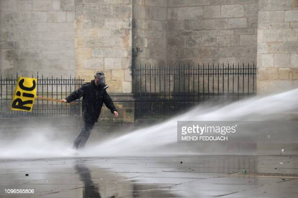 TOPSHOT A man holding a placard reading RIC is seen as a riot police vehicle uses a water cannon to disperse protesters during a yellow vests rally...