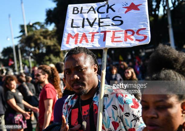 A man holding a placard that reads Black Lives Matters takes part in a demonstration of people including employees of the country's social and...