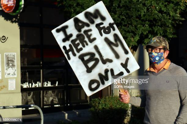 """Man holding a placard walks through the """"Capitol Hill Autonomous Zone"""" in Seattle. The area surrounding Seattle's East Precinct police station, which..."""
