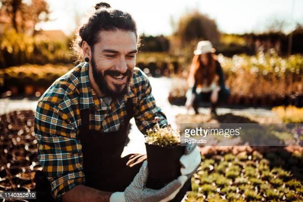 mann hält eine pflanze und lächelt - hipster stock-fotos und bilder