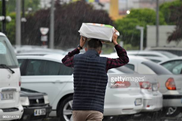 A man holding a plastic bag on his head walks outside a shopping mall during heavy rainfall in the spring season in Ankara Turkey on Sunday May 20...