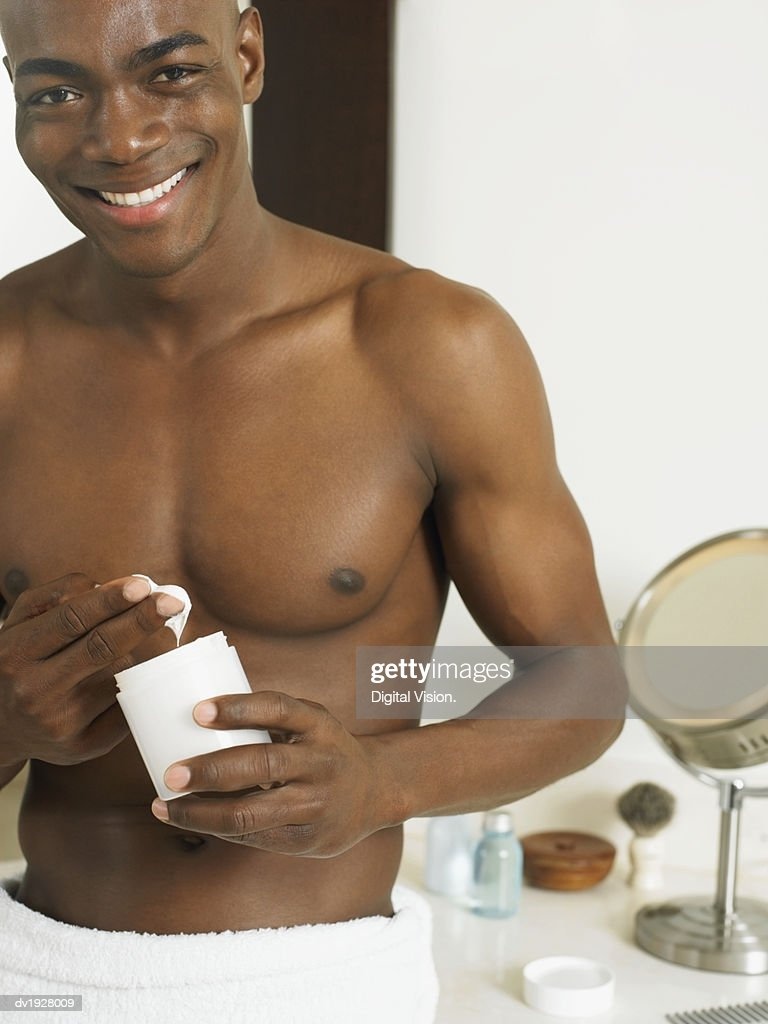 Man Holding a Pot of Moisturizer : Stock Photo