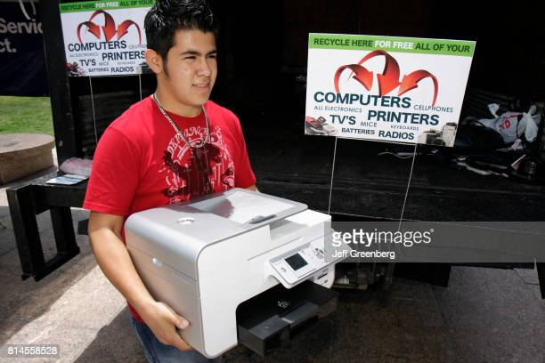 A man holding a printer at the tech recycling station at the Miami Goin' Green event