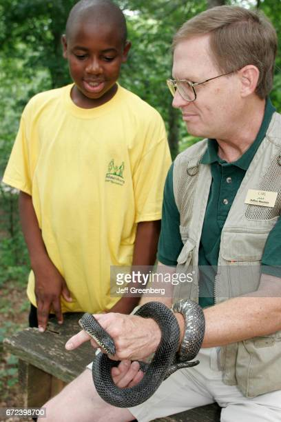 A man holding a rat snake showing summer camp students at the Nature Center in Ruffner Mountain