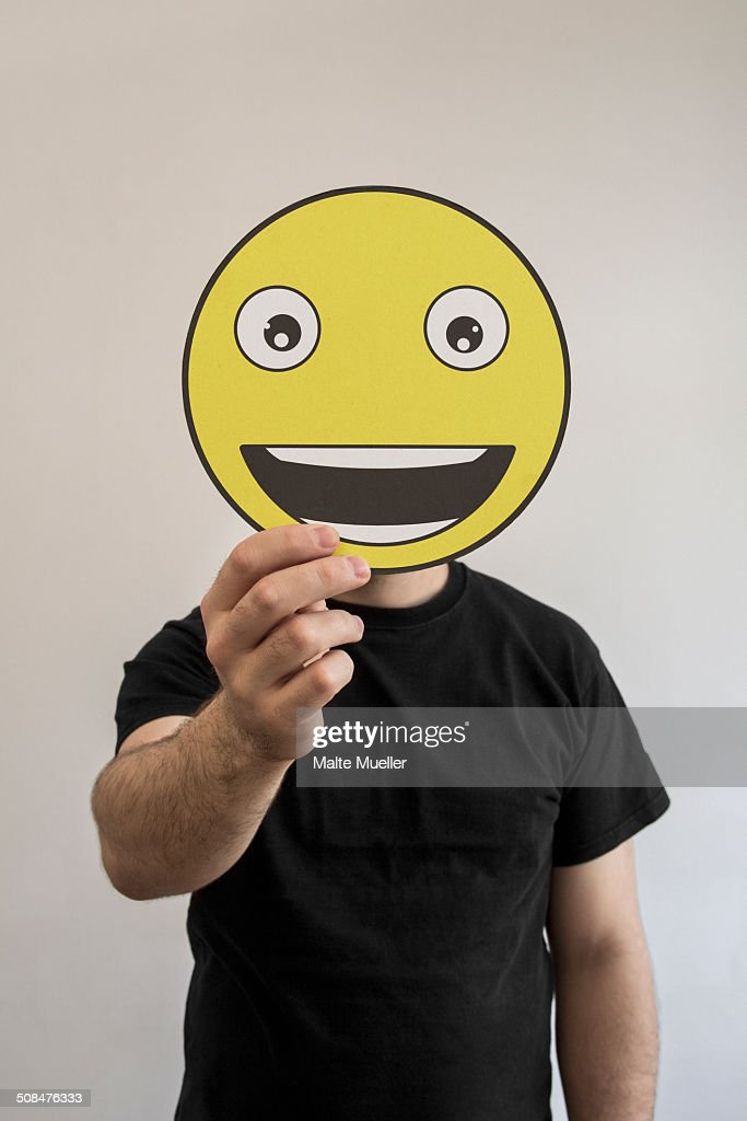 Man holding a really happy emoticon face in front of his face : Stock Photo