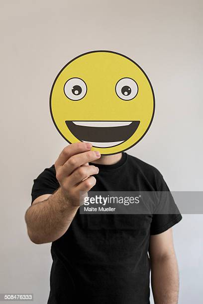 man holding a really happy emoticon face in front of his face - smiley face stock pictures, royalty-free photos & images
