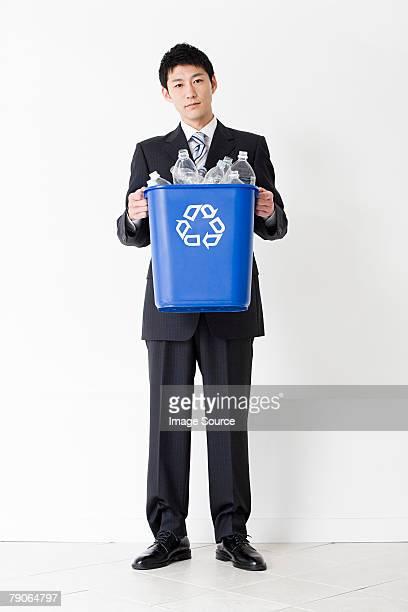 Un homme tenant une poubelle de recyclage