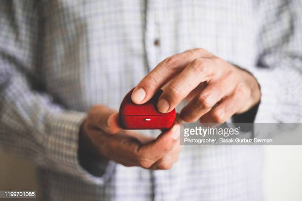 a man holding a red ring box - holding stock pictures, royalty-free photos & images