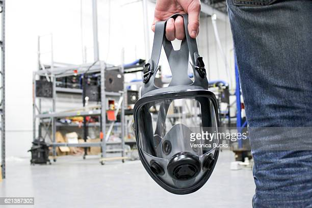 A man holding a respirator mask in an industrial facility