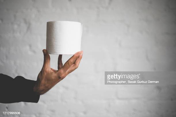 a man holding a roll of toilet paper - human intestine stock pictures, royalty-free photos & images