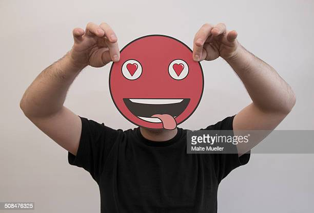 Man holding a romantic emoticon face in front of his face